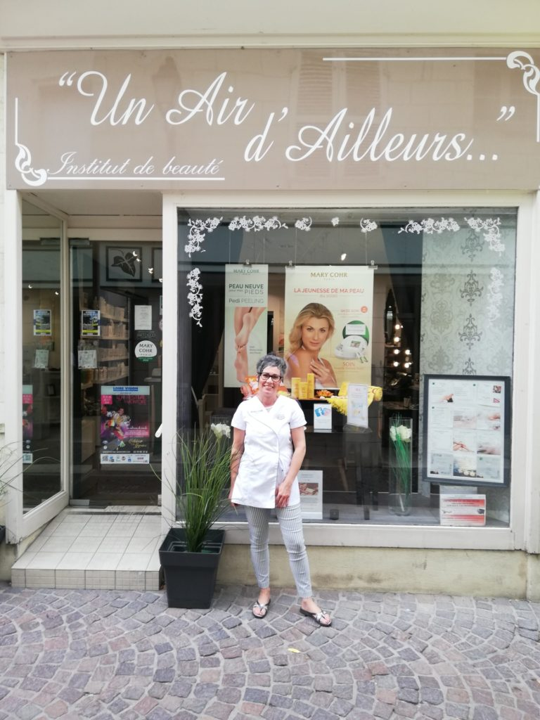 Photo de la propriétaire devant sa boutique